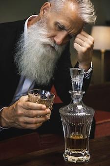 Stylish and handsome bearded senior man drinking whiskey