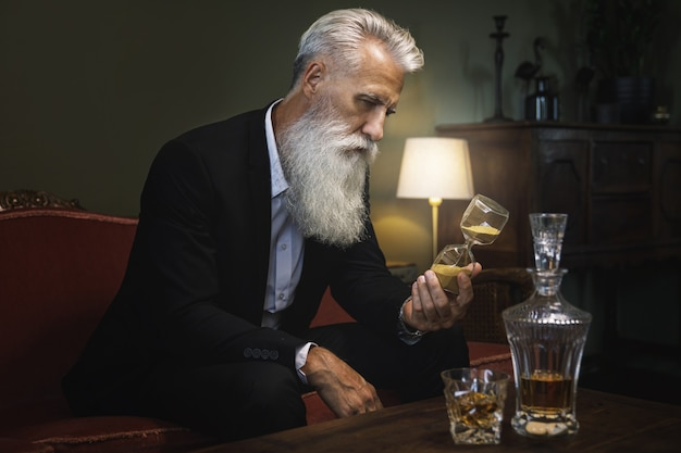 Stylish and handsome bearded senior man is looking at hourglass
