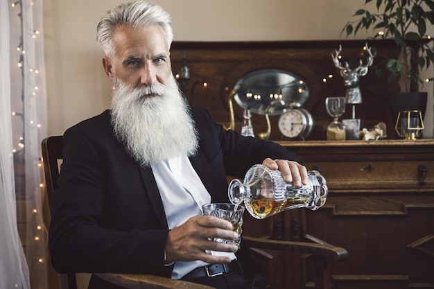 Stylish and handsome bearded senior man pouring whiskey into the glass