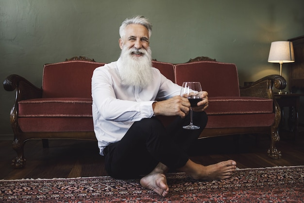Stylish and handsome bearded senior man sitting on the floor and drinking red wine