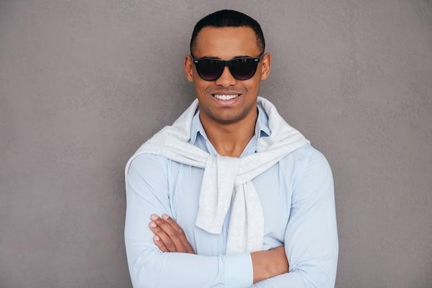 세련된 미남. 팔짱을 끼고 웃고 있는 선글라스를 쓴 자신감 있는 젊은 아프리카 남자