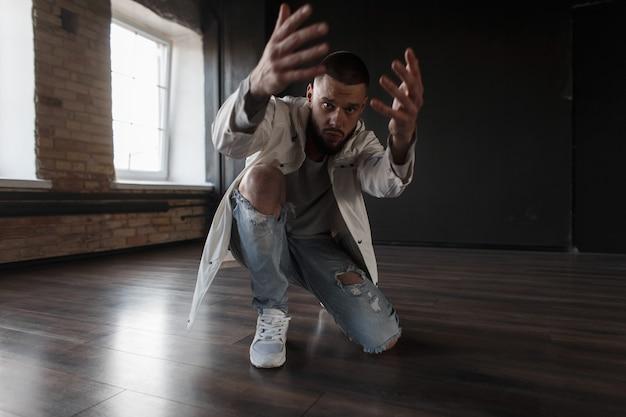 흰색 재킷과 파란색 찢어진 청바지에 세련된 잘 생긴 유행 젊은 남자가 어두운 벽에 포즈