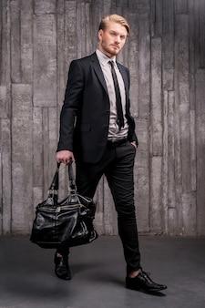세련된 미남. 검은 가방을 들고 formalwear에서 잘 생긴 젊은 남자의 전체 길이