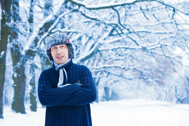 自然の背景の公園で冬のスタイリッシュなハンサムな男
