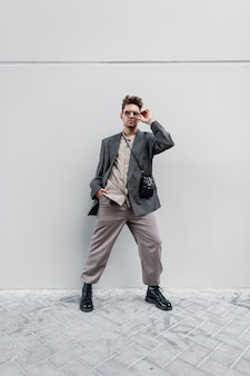 Stylish handsome guy model with sun goggles in a fashionable jacket with a shirt, handbag, trousers and sneakers stands on a gray background