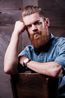 Stylish handsome. handsome young bearded man holding head in hand and looking at camera while sitting on chair