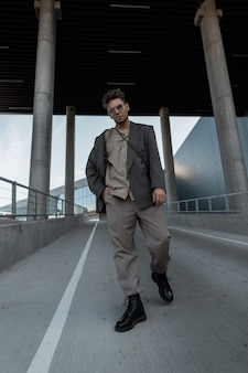 Stylish handsome hipster man model in fashionable outfit with blazer, shirt, trousers and boots walks against the city background.