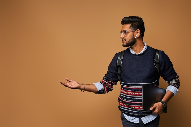 ノートパソコンとバックパックを持ったスタイリッシュなハンサムなインドの学生が手を壁に向けています。