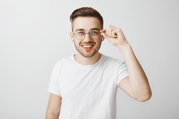 음악 무선 이어폰을 듣고 안경에 세련 된 잘 생긴 남자