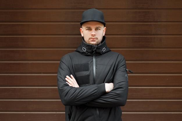 Стильный красавец в черной модной бейсболке и черной зимней куртке стоит и смотрит в камеру возле деревянной стены