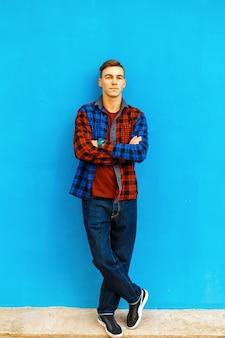ファッショナブルなシャツ、スニーカー、ジーンズを着たスタイリッシュなハンサムな男が、明るい青い壁の近くに立っています。