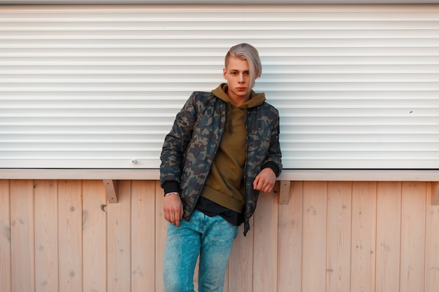 군사 재킷과 벽 근처에 서있는 청바지에 세련된 잘 생긴 남자