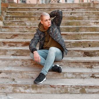 까마귀와 청바지가 달린 군용 재킷에 세련된 잘 생긴 남자가 계단에 앉아있다.