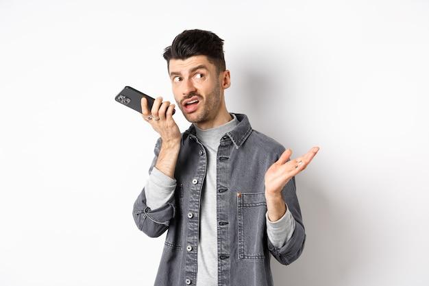 스피커폰에 말하는 세련된 잘 생긴 남자, 입술 근처 스마트 폰으로 음성 메시지를 녹음하고, 뭔가 토론하고 흰색 배경에 서있는 빈 공간에서 옆으로보고 있습니다.