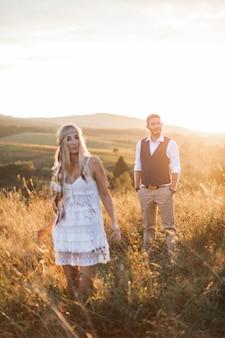 太陽の光の中で自由奔放に生きる服で彼の幸せな女に歩いてスタイリッシュなハンサムな男