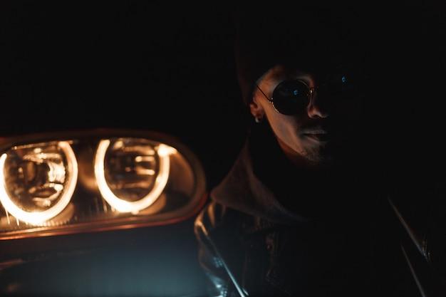 세련된 옷을 입은 선글라스를 쓴 세련된 잘생긴 남자는 밤에 헤드라이트 근처에 앉아 있습니다. 어둠 속에서 남성 실루엣