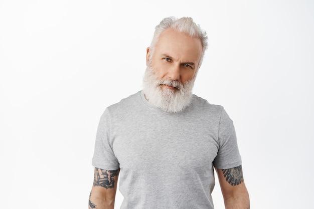 Elegante bell'uomo maturo con corpo tatuato e barba lunga, inclina la testa e guarda fiducioso macho davanti, fissando serio, in piedi in maglietta grigia contro il muro bianco