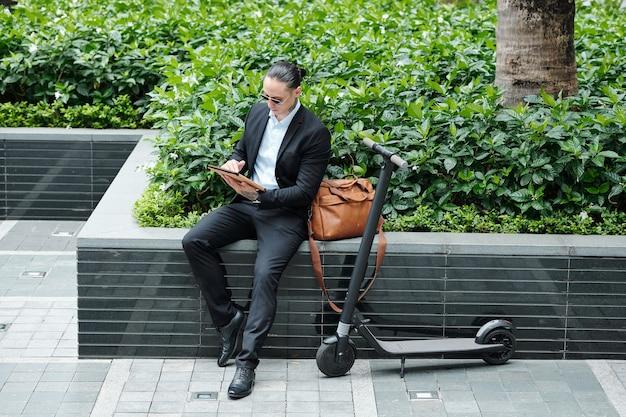 彼の電動スクーターの隣に屋外に座って、デジタルタブレットで記事を読んでいるスタイリッシュなハンサムな多民族の起業家