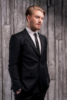 Стильный красавчик. вид сбоку на красивого молодого человека в строгой одежде, держащего руки в карманах и смотрящего в сторону