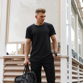 Stylish handsome young american hipster model man with hairstyle in black t-shirt with fashion bag standing on the street near the wooden building
