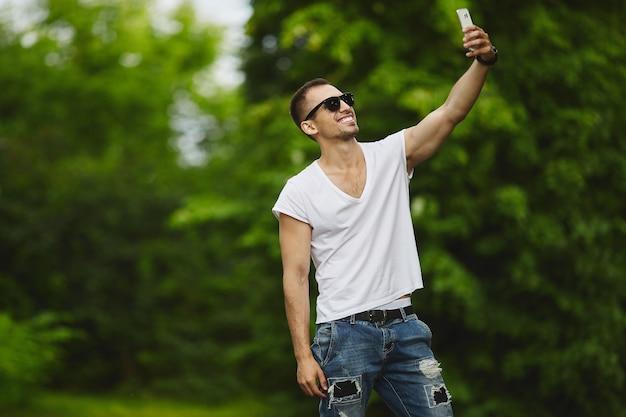 白いtシャツとジーンズを着たスタイリッシュなハンサムな若いアスリート男性がスマートフォンで自分撮りをします