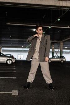 駐車場でファッショナブルな服のスーツを着たスタイリッシュなハンサムな若いビジネスマン。メンズアーバンスタイルとファッション