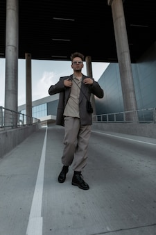 Stylish handsome young businessman man in a jacket, trousers, shirt and boots with sunglasses walks in the city. urban male style