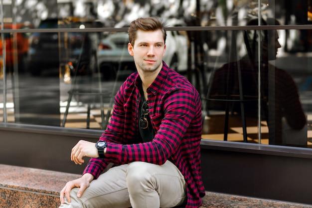 Elegante giovane uomo d'affari bello seduto per strada, sorriso incredibile, capelli e occhi marroni, indossa una camicia a quadri hipster e pantaloni beige, occhiali da sole e orologi, in posa vicino al ristorante.