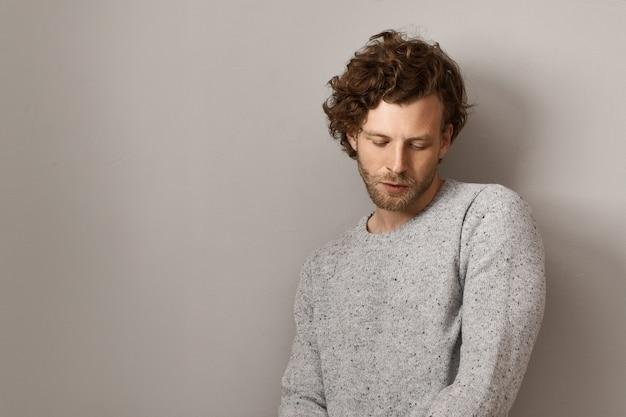 Elegante bell'uomo giovane europeo con barba tagliata e voluminosi capelli rossicci vestito in un accogliente maglione grigio caldo, guardando in basso con timida espressione facciale, pensando a qualcosa