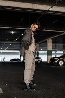 シャツ、ズボン、ジャケット、黒い靴とファッショナブルなビジネス服のスタイリッシュなハンサムな若い男モデルが駐車場に立っています