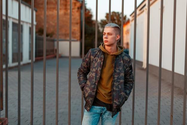울타리 근처 청바지와 유행 군사 재킷에 세련된 잘 생긴 젊은 남자