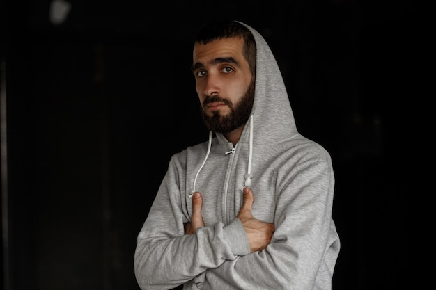 Stylish handsome young man with a beard in gray hoodie on a dark wall