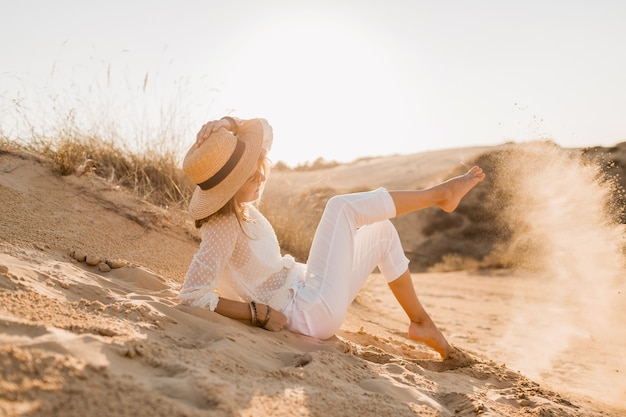 Stylish happy attractive smiling woman posing in desert dressed in white clothes wearing straw hat and sunglasses on sunset