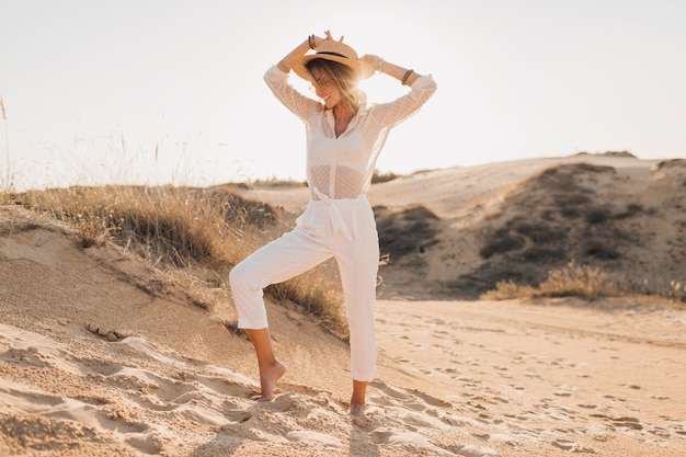 Stylish happy attractive smiling woman posing in desert sand dressed in white clothes wearing straw hat and sunglasses on sunset