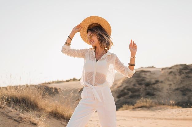 Elegante donna sorridente attraente felice in posa nella sabbia del deserto vestita in abiti bianchi che indossa cappello di paglia e occhiali da sole sul tramonto