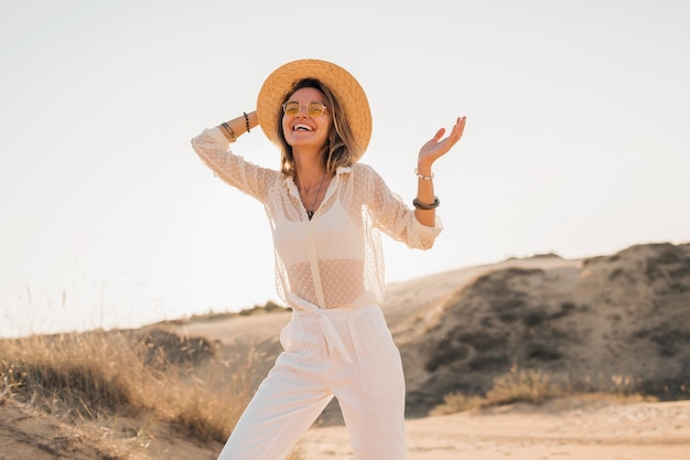 Stylish happy beautiful smiling woman posing in desert sand in white outfit wearing straw hat and sunglasses on sunset