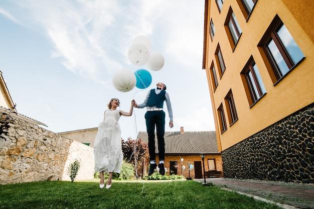 Стильные счастливые невеста и жених держат воздушные шары в руках и прыгают