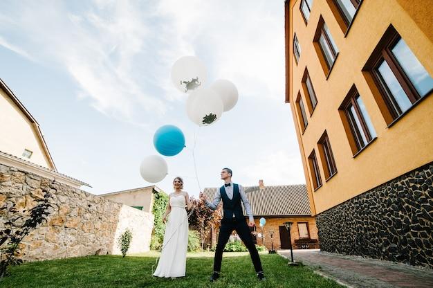 Стильные счастливые невеста и жених держат воздушные шары в руках и прыгают.