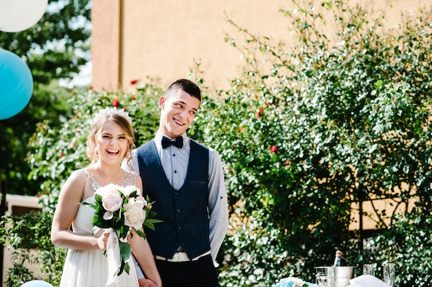 Стильная счастливая невеста с букетом пионов и жених держатся за руки