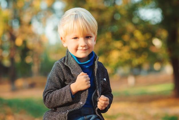 Стильный счастливый ребенок на осенней природе. красивый мальчик с современной прической. мода, осень и детство