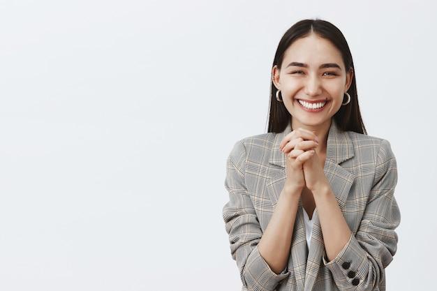 ジャケットを着たスタイリッシュな幸せなヨーロッパの女性、胸に手を握りしめ、嬉しそうに笑って、素晴らしいニュースを受け取って喜んで、灰色の壁の上に立っています