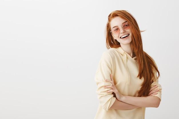 Стильная счастливая великолепная рыжая девушка скрещивает руки на груди и улыбается