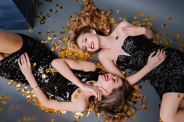 Stylish happy party image from above two attractive young women in luxury black dresses laying in golden tinsels. having fun, laughing, smiling, expressing true positive emotions.