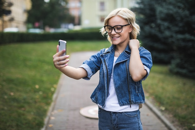 ジーンズスイートのスタイリッシュな幸せなかなりファッションブロンドの女の子女性は、朝市で彼女の電話でselfieを作る