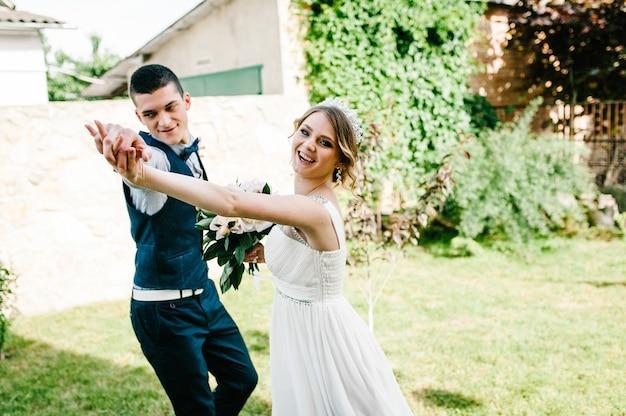 Стильная счастливая улыбка невесты и жениха держаться за руки и танцевать, бегать, идти