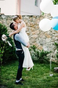 Стильные счастливые улыбки жениха и невесты держатся за руки невесты и обнимаются.