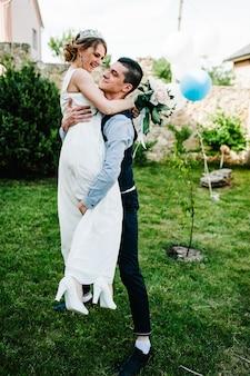 Стильная счастливая улыбка невесты, жениха держит в руках и танцует.