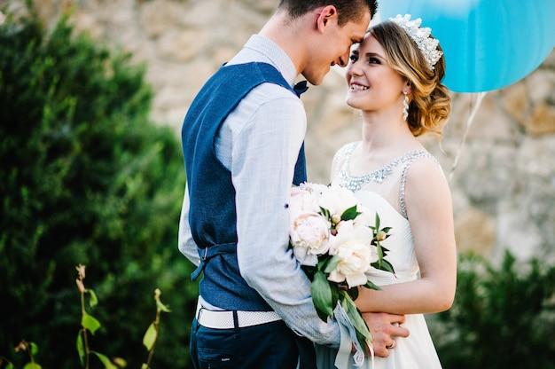 Стильная счастливая улыбка невесты с букетом пионов и жених держит воздушные шары в руках и обнимает