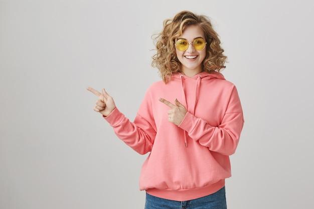 Стильная счастливая девочка-подросток в солнцезащитных очках показывает путь, продвигает рекламу