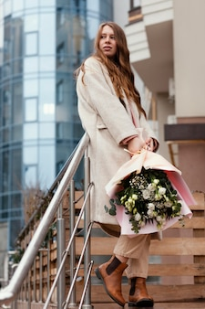 Stylish happy woman holding bouquet of flowers outdoors